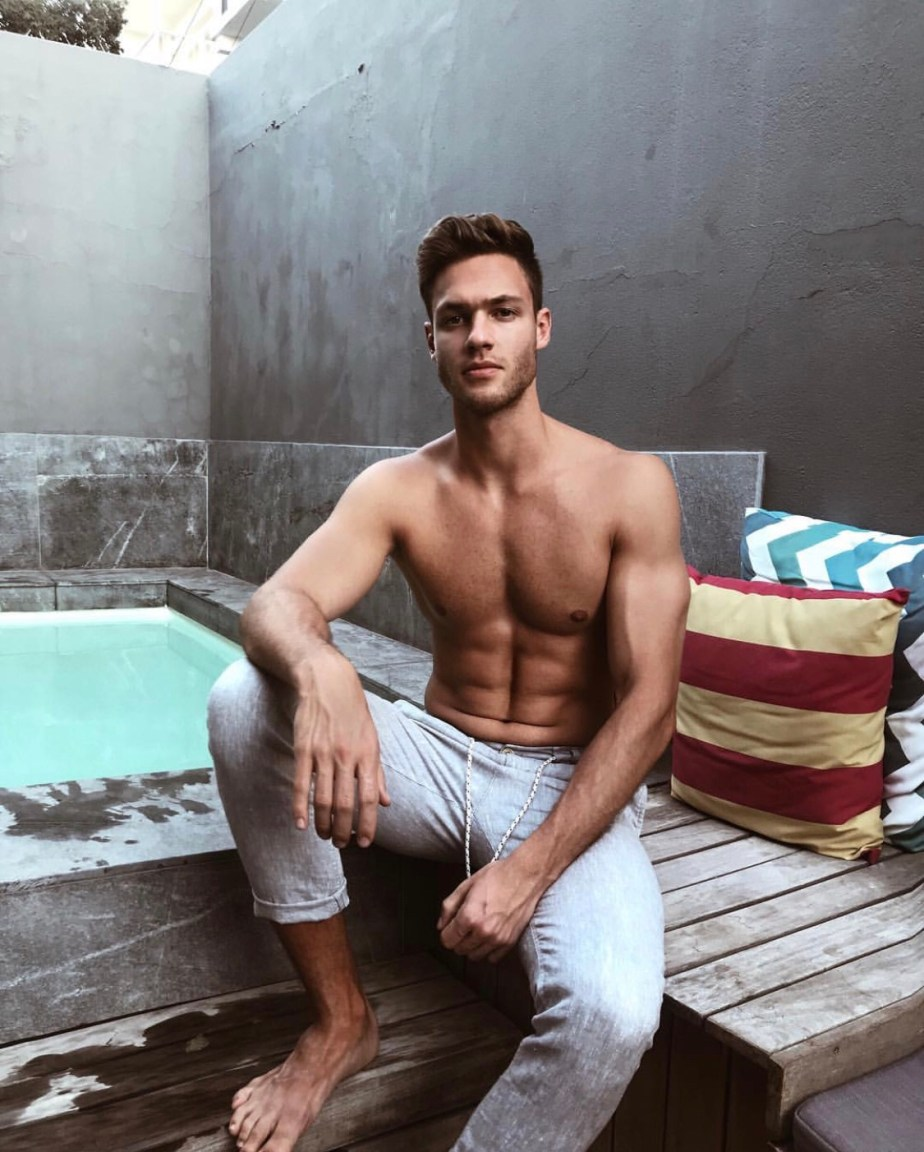 Tobias Reuter barefoot and shirtless by the pool