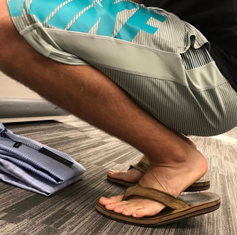 Guy barefoot in flip flops and Nike shorts clothes shopping