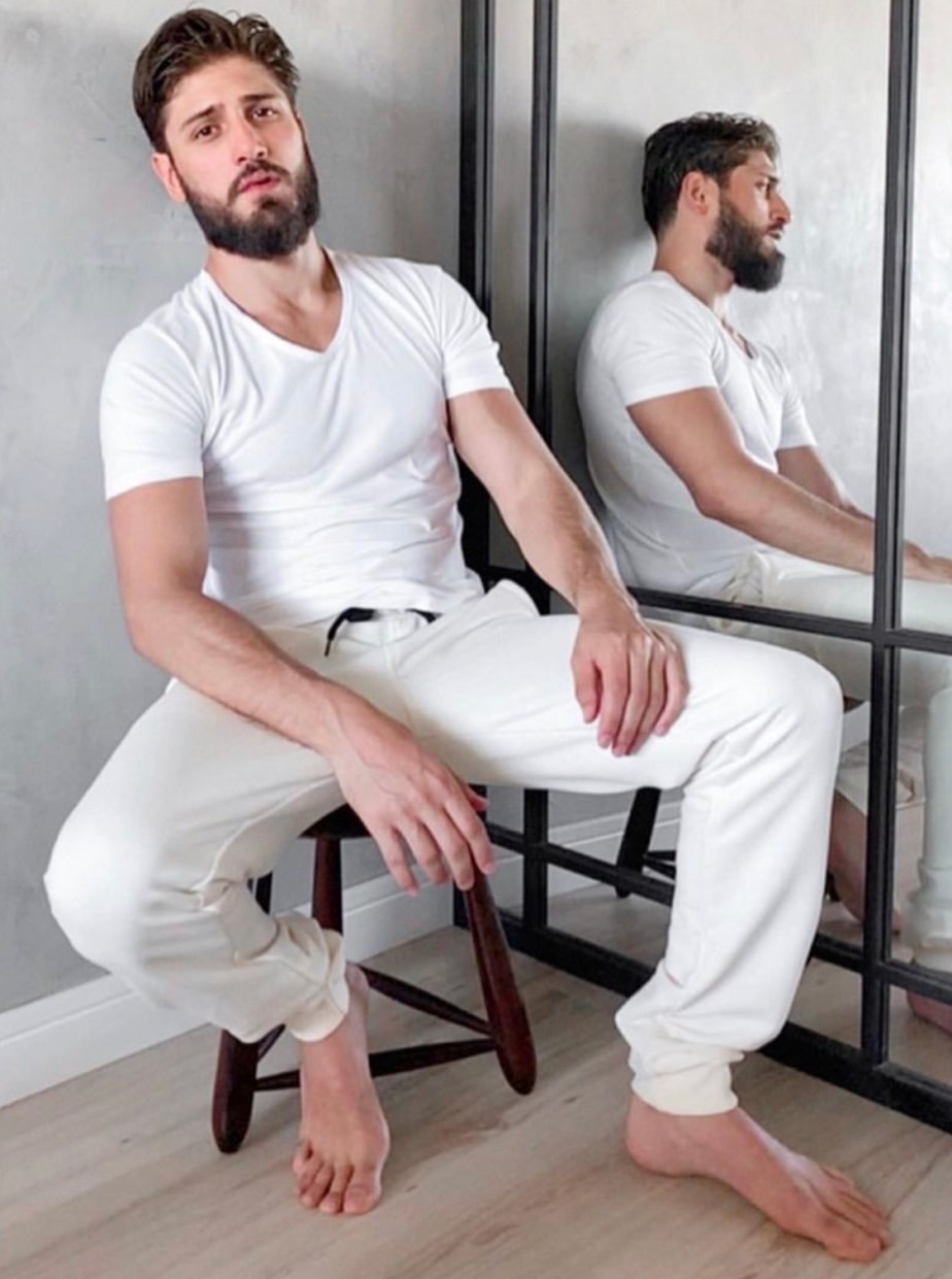 Bearded Daniel Rochaaz sitting down showing off his bare feet and toes