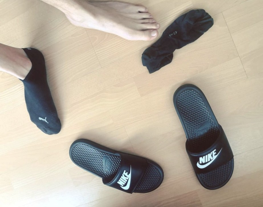 sneaks_tiral barefoot out of black Puma ankle socks and Nike slides