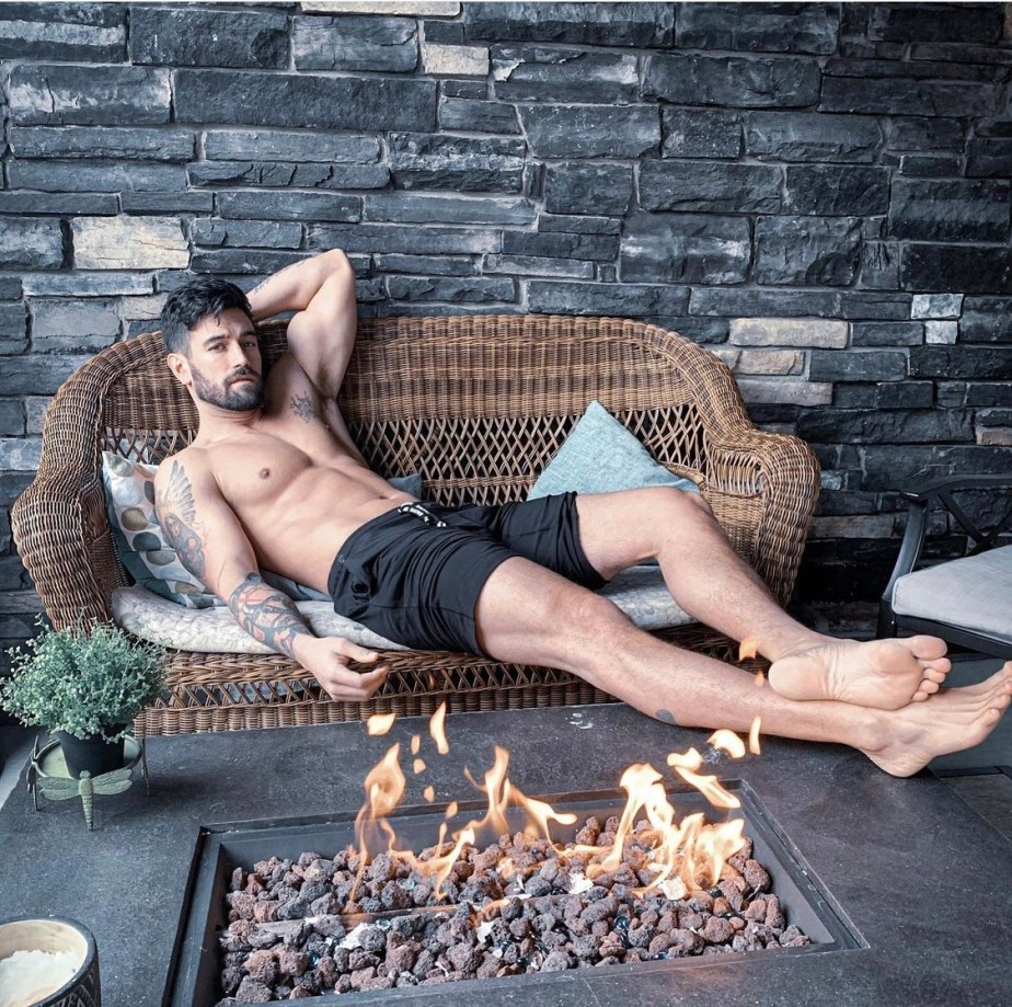 str3lly bearded, shirtless with his bare feet up