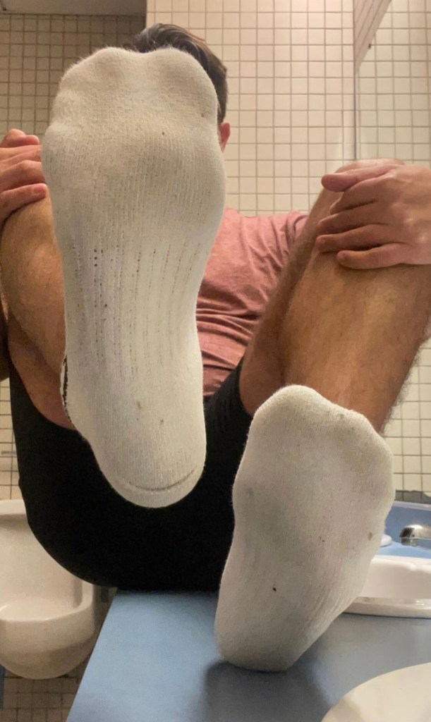 socksprof shows off his white socks by the bathroom sink