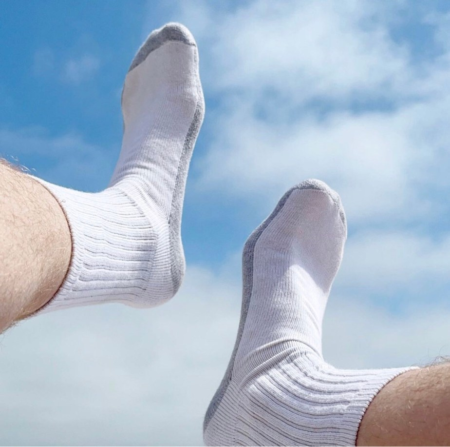 darioxity's white and gray crew socked feet in the air