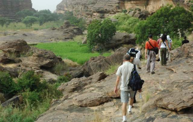 A group of travelers trek on the Bandiagara cliff, heading to the Dogon villages
