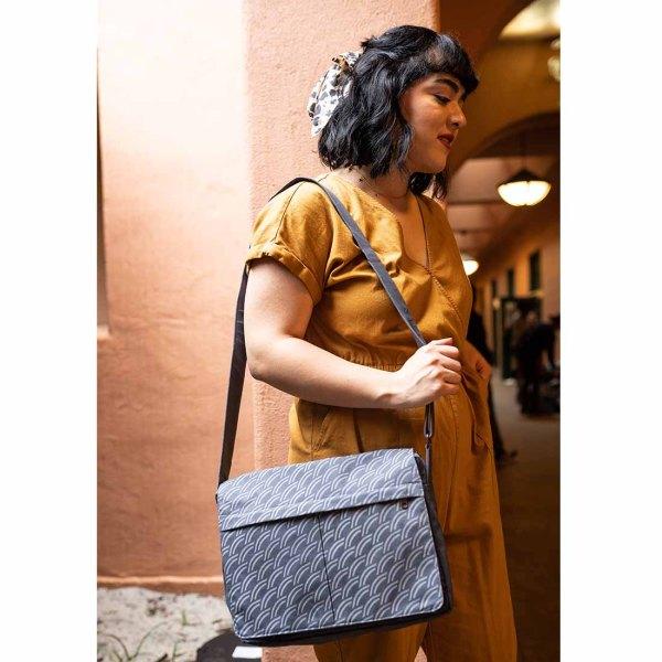 woman with dark grey canvas messenger bag