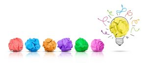 Paper ball forming a lightbulb with other multi-colored paper balls around, white background