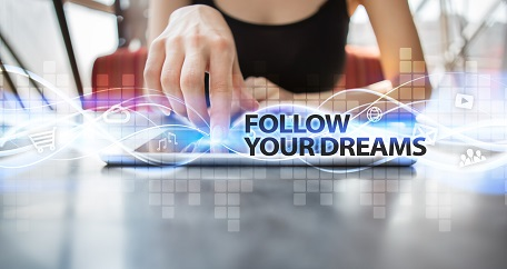 Woman using tablet pc and selecting follow your dreams.