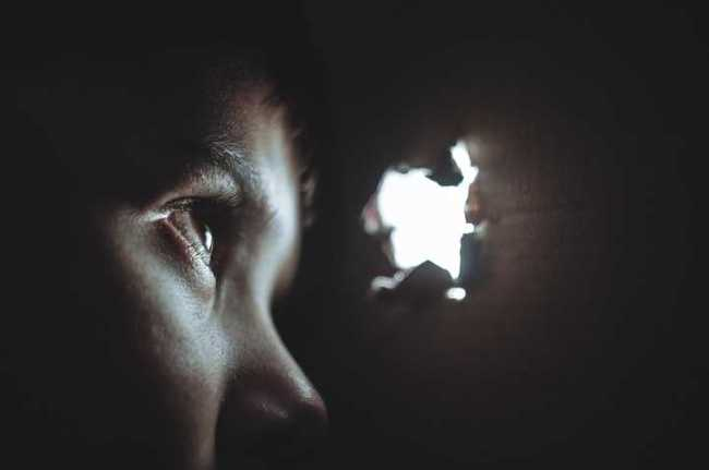 boy in the dark looking through a hole