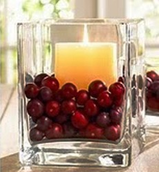 candle and cranberries in glass jar centrepiece
