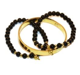 MamaBella AD0004 Lucky Beads Golden RVS Set is een set voor dames bestaande uit twee identieke armbanden gemaakt van zwarte glaskralen gecombineerd met goudkleurige bolletjes, voozien van een goudkleurig bedeltje met een klavertje aan, alsook een goudkleurige roestvrije armband