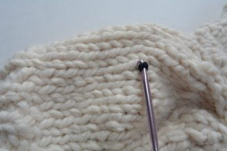 Pull yarn up through hat