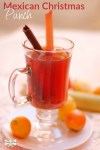 Glass cup with Mexican Christmas punch and a cinnamon stick and sugar cane