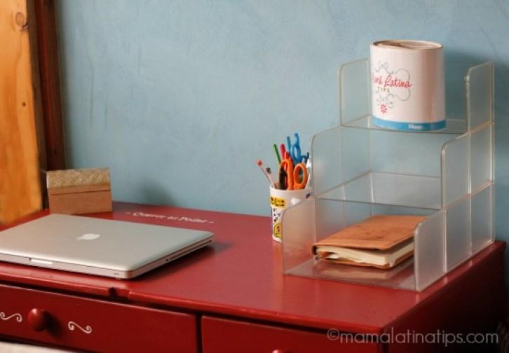 Un escritorio rojo con una computadora, libreta y lapiceros