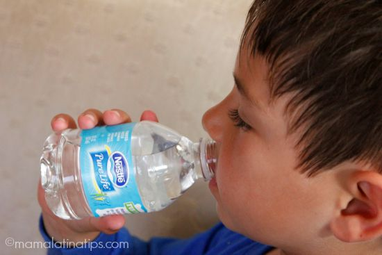 little kid drinking from a water bottle