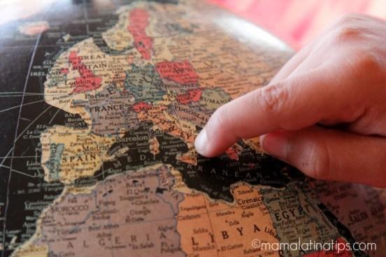 Kid pointing Italy in a globe - mamalatinatips.com