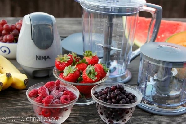 Ninja food processor and fruit on a wooden table