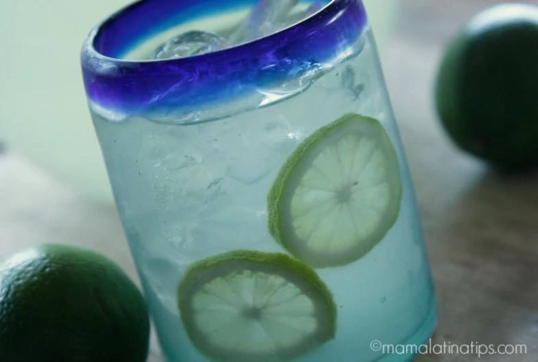 A Mexican glass with blue rim with lime agua fresca and lime slices inside.