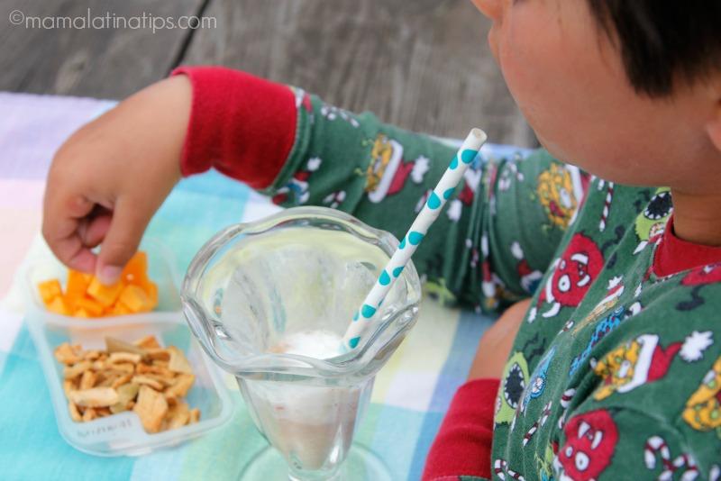 kid eating chocolate milk and a nutritious snack - mamalatinatips.com