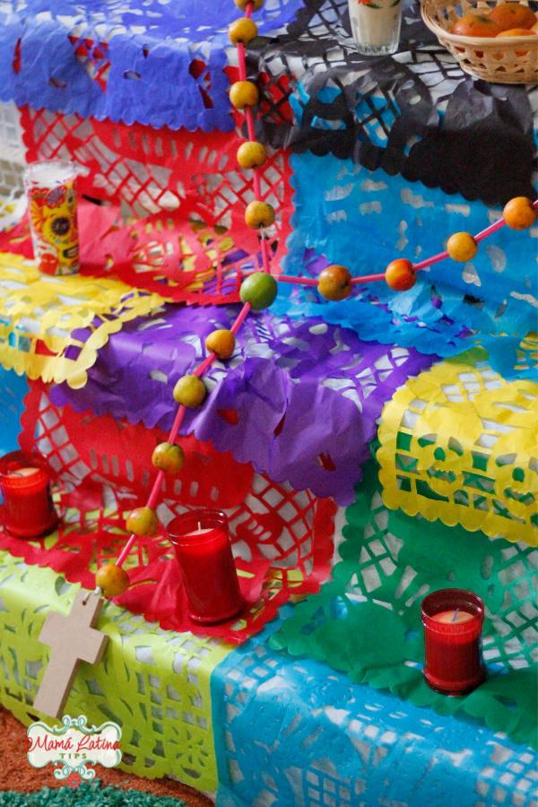 Altar de muerto con papel picado y rosario hecho de tejocotes.