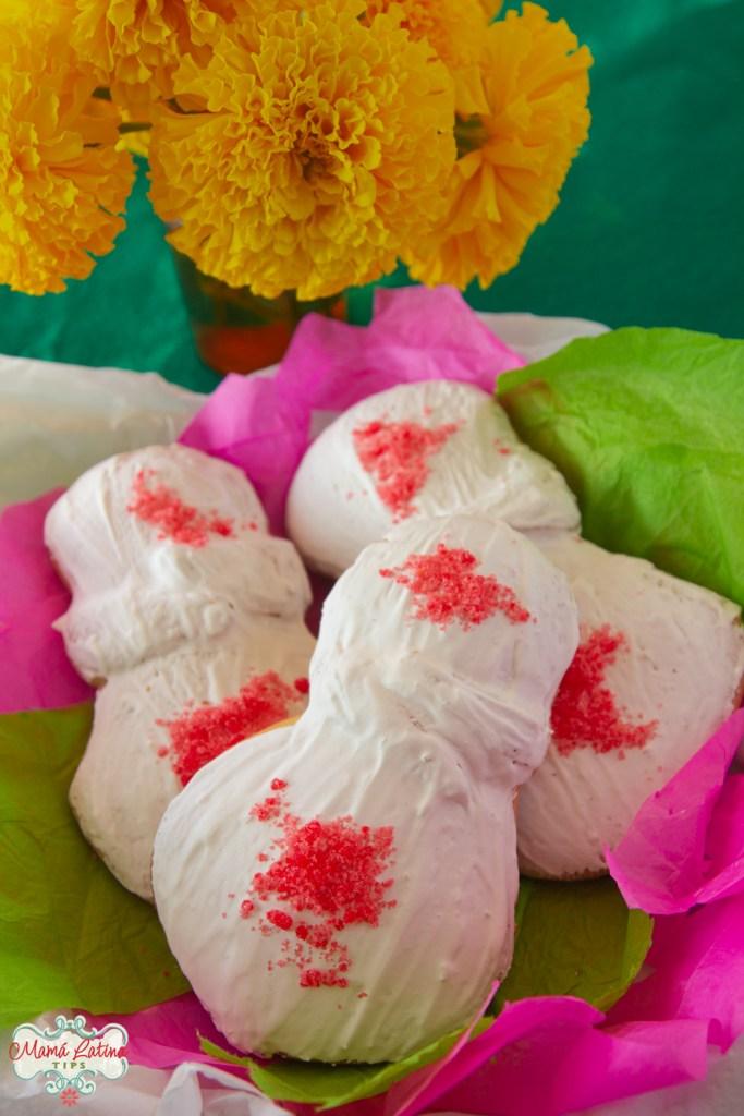 pan de muerto cubierto de un glaseado blanco y azúcar rosada