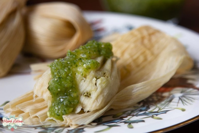 green tamales with chicken on a holiday plate