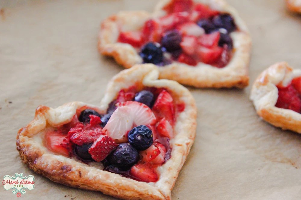 Two heart-shaped fruit tarts on top of beige parchment paper