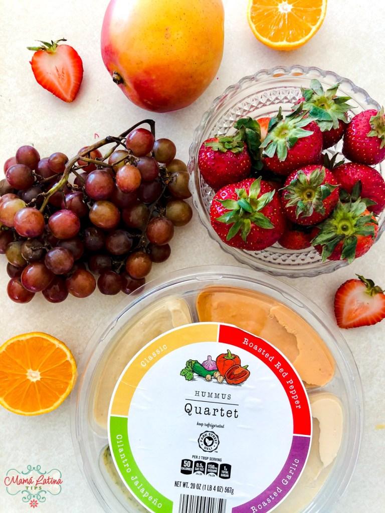 Un paquete con cuatro tips de hummus, rodeado de fresas, uvas, un mango y naranjas