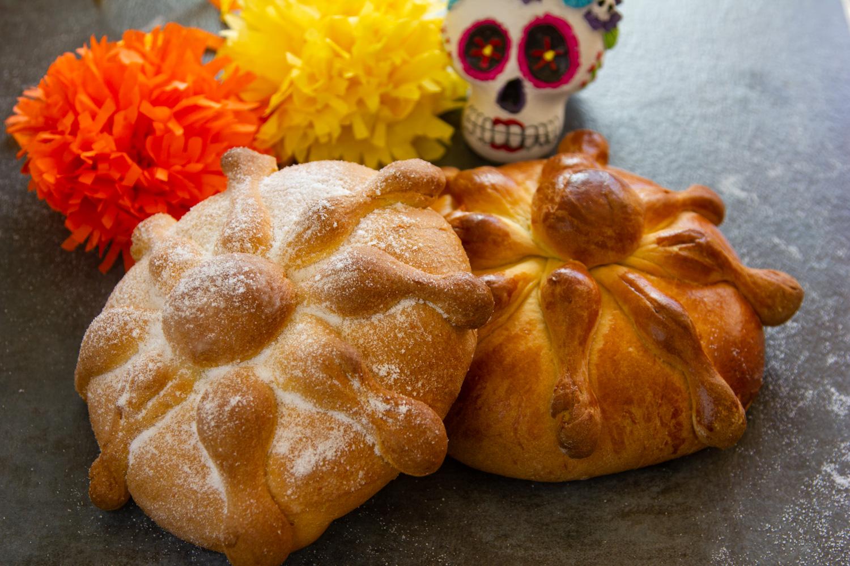 dos panes de muerto, uno con azúcar, otro con barnizado de huevo