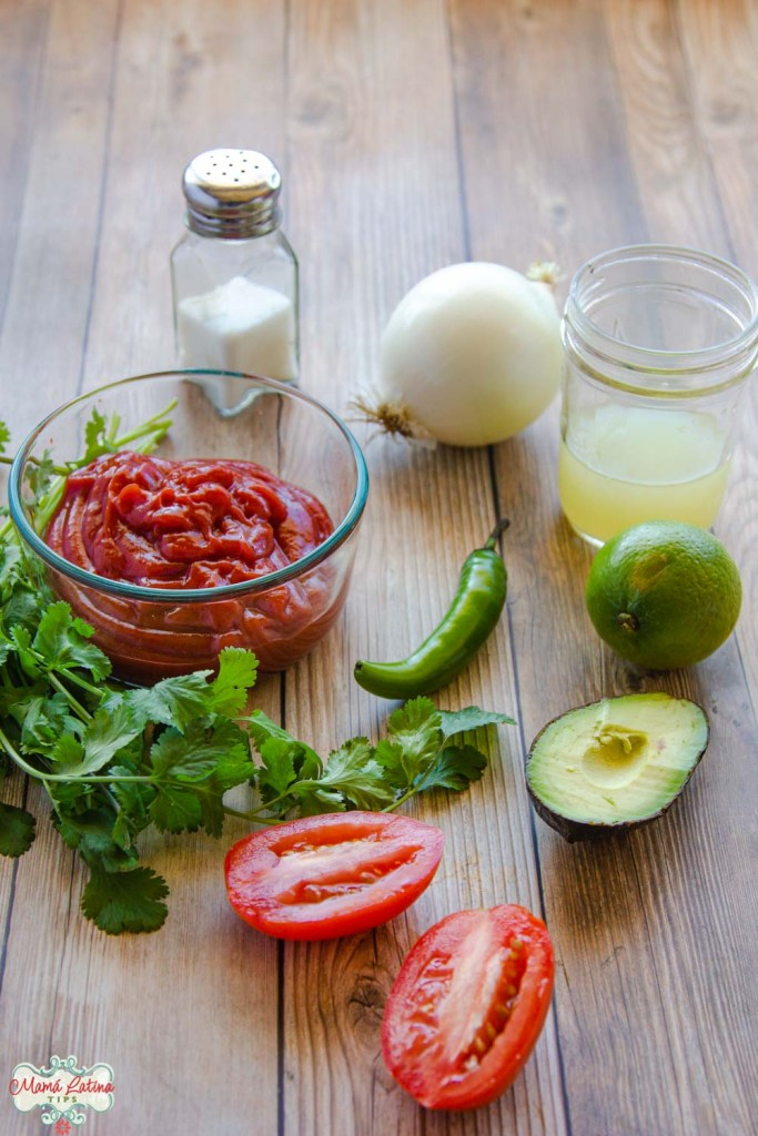 serrano pepper, cilantro, tomatoes, lime juice, onion, salt shaker and ketchup on a wooden table.