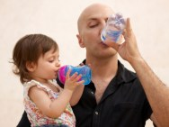 143224998-baby-girl-and-father-drinking-water-together-gettyimages