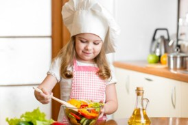 kid making salad at kitchen