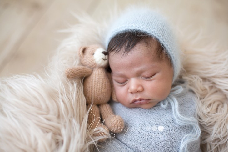 Newborn baby boy snuggling tiny teddy bear