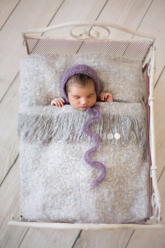 Snug newborn girl in a bed wearing purple bonnet hat