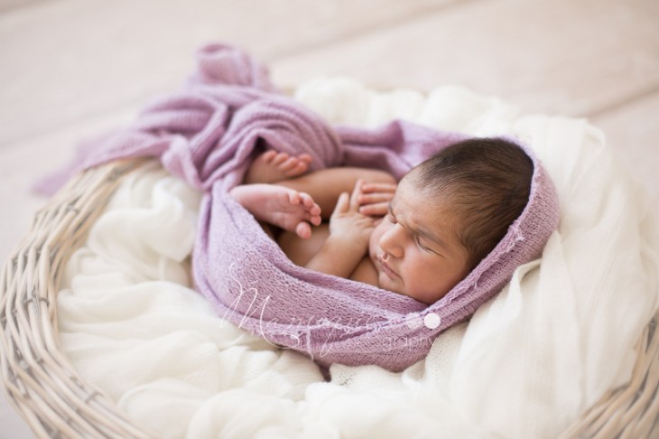 frowning newborn baby girl wrapped in purple on cream soft blanket