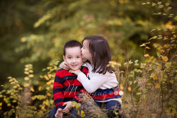 Big sister giving little brother a kiss sitting surrounded by fall leaves