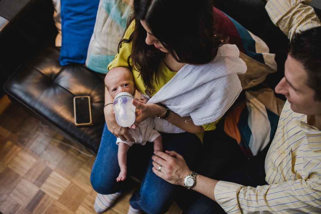 new parents feeding a newborn baby with a bottle