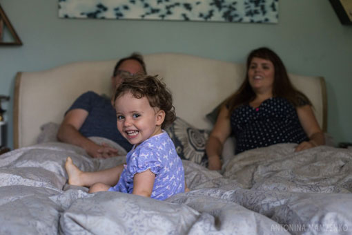 toddler playing on a bed with her pregnant mother