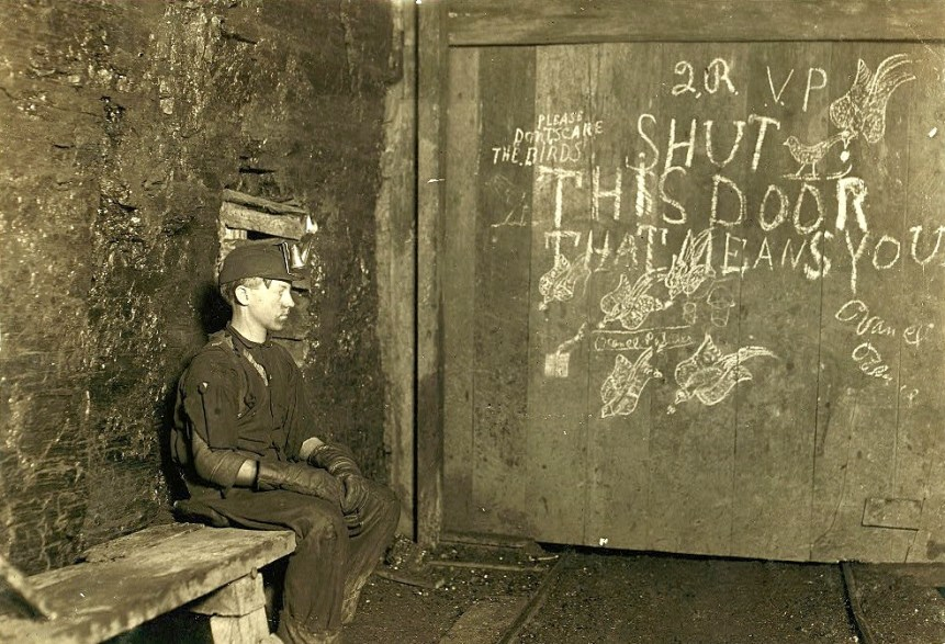 Vance, a Trapper Boy, 15 years old. Has trapped for several years in a West Va. Coal mine. $.75 a day for 10 hours work. All he does is to open and shut this door: most of the time he sits here idle, waiting for the cars to come. On account of the intense darkness in the mine, the hieroglyphics on the door were not visible until plate was developed. Location: West Virginia. Photo by Lewis Wickes Hine, 1908 September.