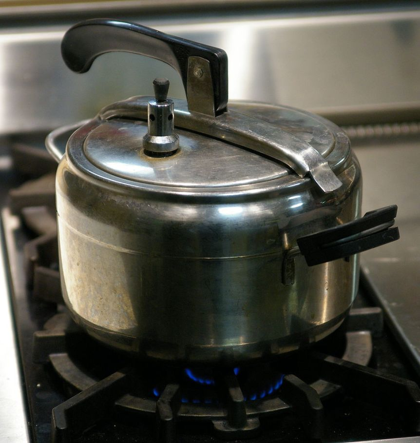 """Pressure cooker with a simple regulator and an oval lid"""". (c) 2009 Hustvedt (CC BY SA 2.0) Via Wikimedia Commons."""