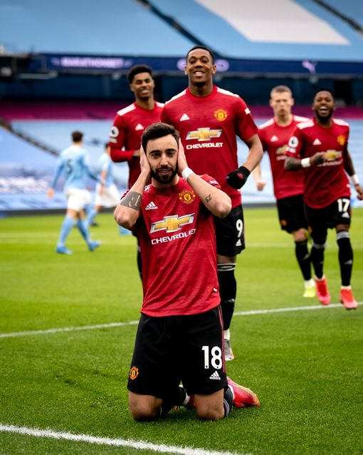 MANCHESTER, ENGLAND - MARCH 07: Bruno Fernandes of Manchester United celebrates scoring a goal to make the score 0-1 during the Premier League match between Manchester City and Manchester United at Etihad Stadium on March 7, 2021 in Manchester, United Kingdom. Sporting stadiums around the UK remain under strict restrictions due to the Coronavirus Pandemic as Government social distancing laws prohibit fans inside venues resulting in games being played behind closed doors. (Photo by Ash Donelon/Manchester United via Getty Images)