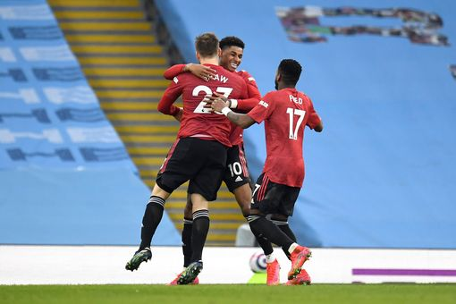 MANCHESTER, ENGLAND - MARCH 07: Luke Shaw of Manchester United celebrates with Marcus Rashford and Fred after scoring their side's second goal during the Premier League match between Manchester City and Manchester United at Etihad Stadium on March 07, 2021 in Manchester, England. Sporting stadiums around the UK remain under strict restrictions due to the Coronavirus Pandemic as Government social distancing laws prohibit fans inside venues resulting in games being played behind closed doors. (Photo by Peter Powell - Pool/Getty Images)