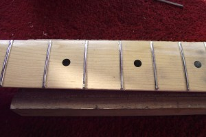 Showing the fret tops all touched by the sanding bar