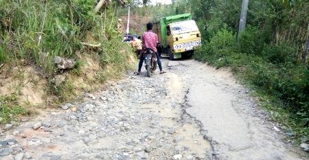 seorang pengendara sepeda motor menunggu lewat satu truk pelan-pelan melewati jalur Pakantan-Muara Sipongi akibat badan jalan yang hancur