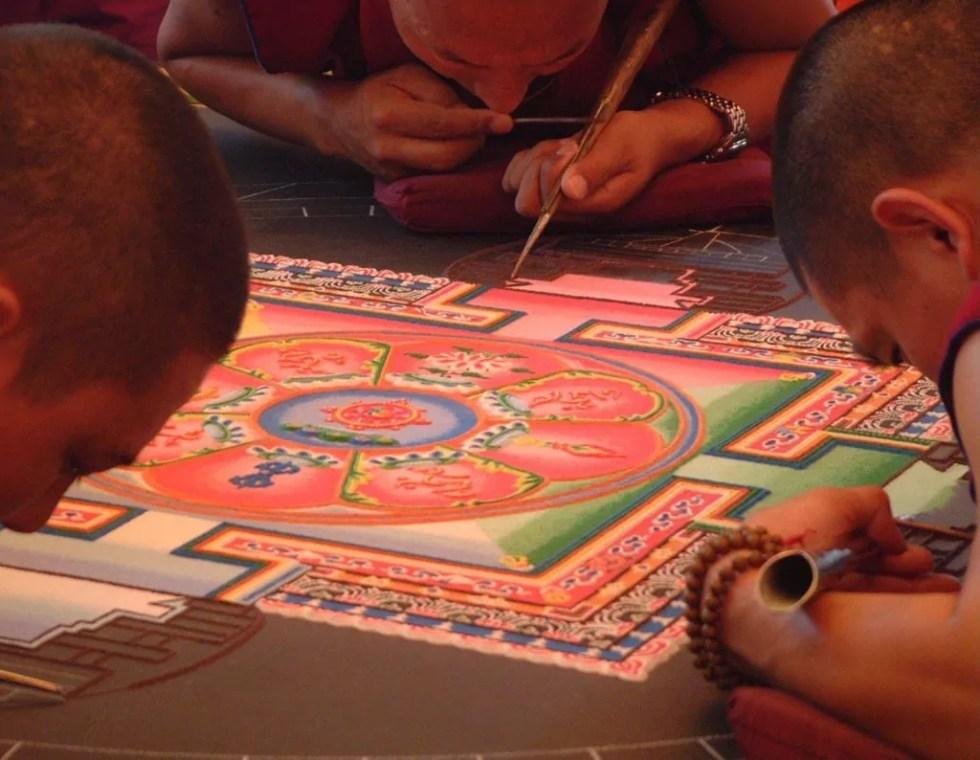monaci buddisti che disegnano un mandala di sabbia