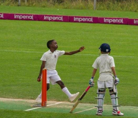 Help kids commit Black boy bowling at a cricket match. Black boy playing sport. Commitment contract
