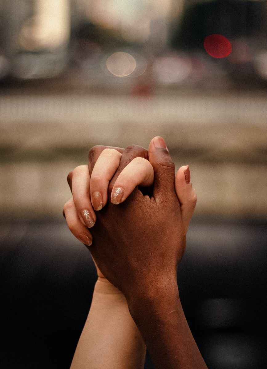 multiethnic couple holding hands together in park