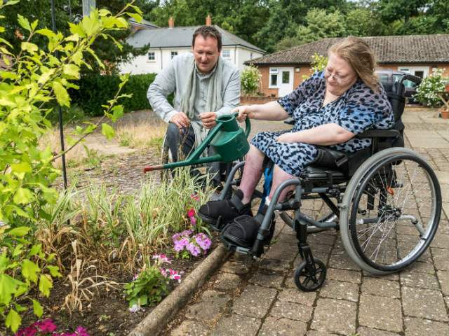 Mark Lane with a resident watering the garden. Picture; Leonard Cheshire