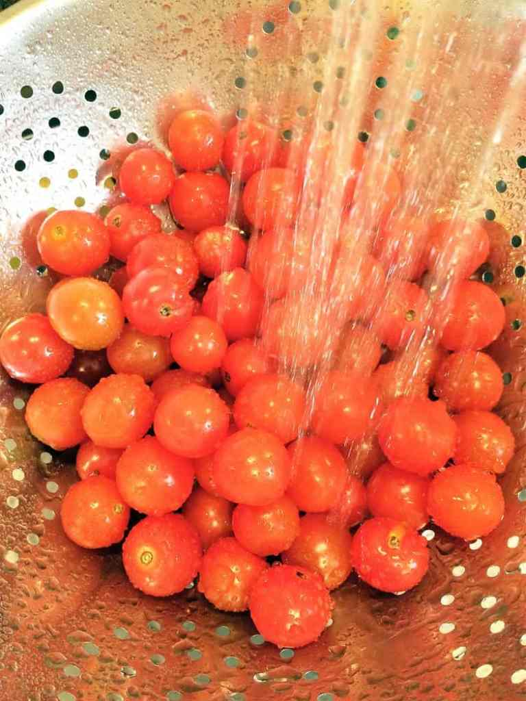 cherry tomatoes in a colander being rinsed