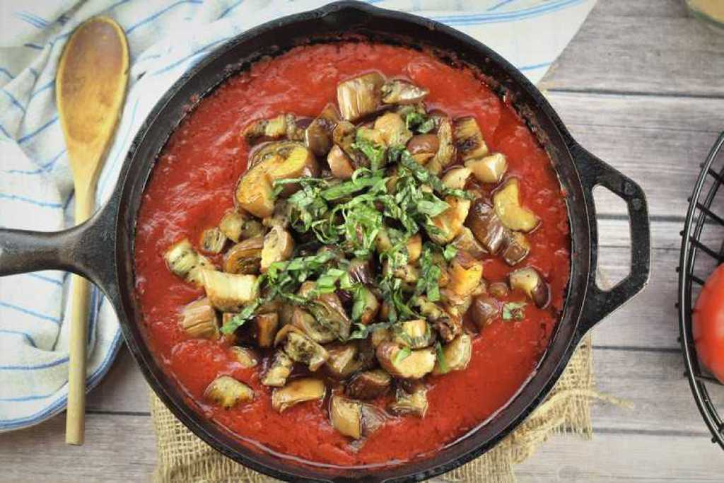 skillet with tomato sauce, eggplant pieces topped with chopped basil
