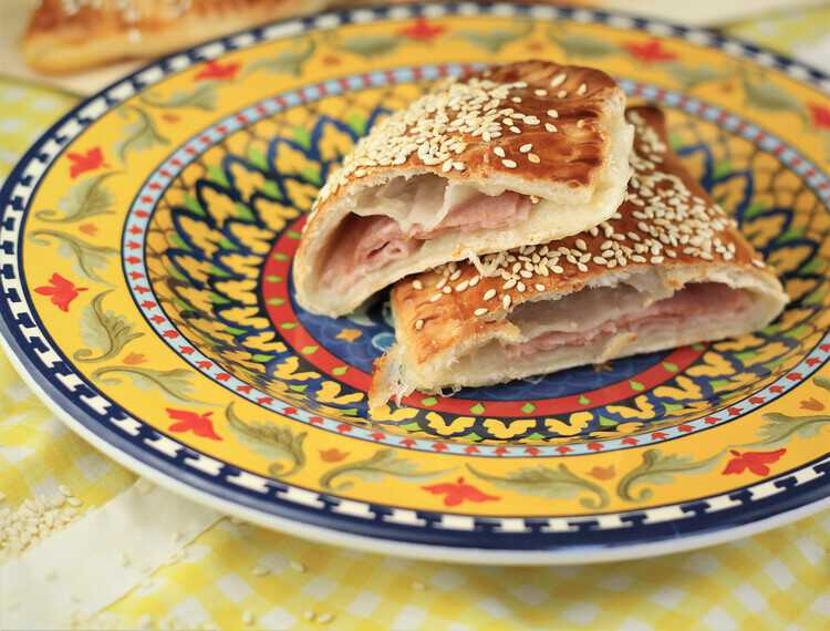 calzone with prosciutto cotto and mozzarella sliced in half served on a colorful plate